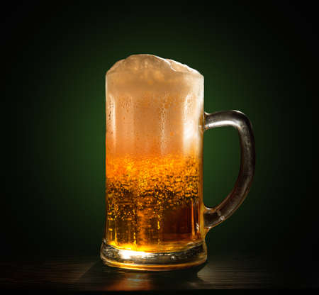 A glass of fresh, cold beer close-up on a black background