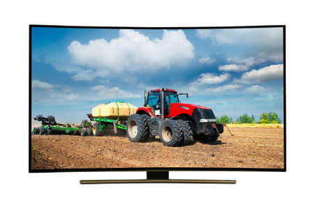 monitor isolated on white. Modern tractor conducts spring field work in the field . Modern, elegant TV 4 K, with incredibly beautiful colors of the image . Stock Photo