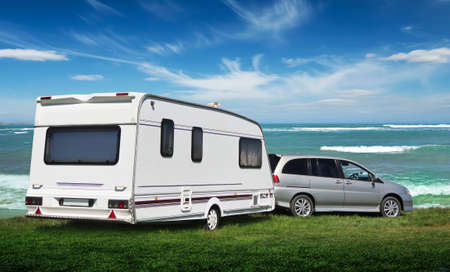 The caravan stands on the Vedic lawn by the sea. The family went on vacation to nature. Stock Photo