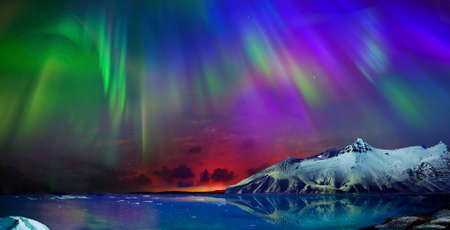 Schitterend, onwerkelijk mooi nachtzicht van de weerspiegeling van het noorderlicht in het water van de oceaan en de met sneeuw bedekte bergen. Night Northern Lights is gewoon een geweldig gezicht.