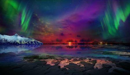 Magnifique vue nocturne magnifique et irréelle du reflet des aurores boréales dans l'eau de l'océan et des montagnes enneigées. Les aurores boréales nocturnes sont juste un spectacle incroyable.