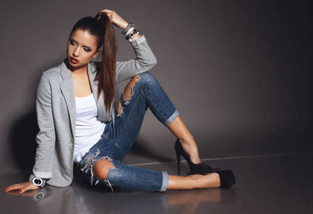 fashion studio photo of beautiful young woman with dark hair wears casual clothes with accessories