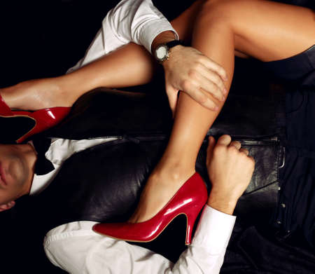 Legs and heels: fashion studio photo of beautiful sensual impassioned couple. office love story