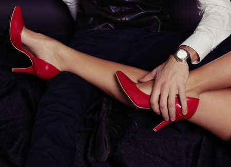 office love story.womans legs in red shoes
