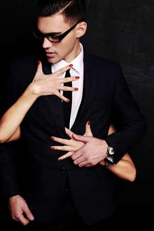 黒い髪と彼を抱きしめる彼女の彼女の手でハンサムな官能的な男のファッション スタジオ写真
