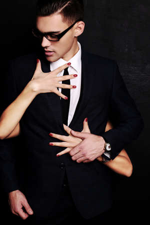 fashion studio photo of handsome sensual man with dark hair and her girfriend's hands embracing him