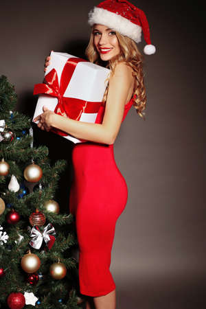 Christmas photo of sexy woman with curly blond hair in a red Santa-hat and red dress with charming smile  holding a gift-boxes near Christmas tree Archivio Fotografico