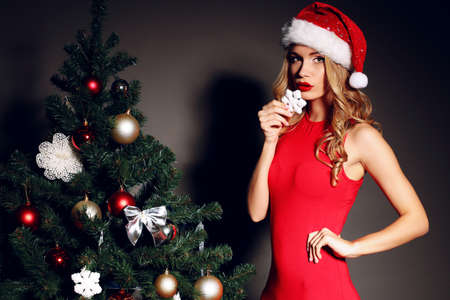 Christmas photo of sexy woman with curly blond hair in a red Santa-hat and red dress holding a deco near Christmas tree