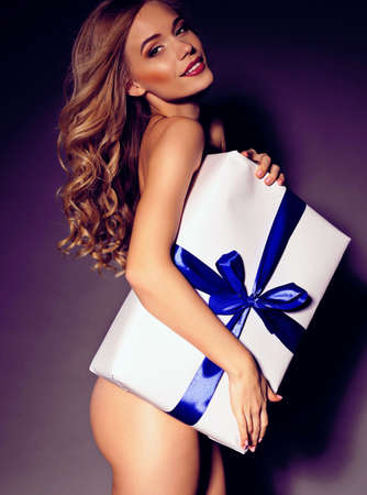 woman naked body: festive photo of sexy blond woman with curly hair and beautiful charming smile holding a big present white gift with blue bow