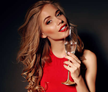 sexy photo: party photo of sexy lady in red dress with red lips and blond beautiful curly hair, holding a glass with shampagne