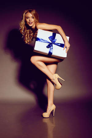 holiday photo of sexy blond woman with curly hair and beautiful charming smile holding a big present white gift with blue bow