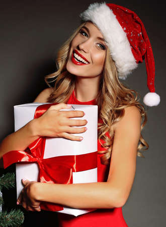 red white: Christmas photo of sexy woman with curly blond hair in a red Santa-hat and red dress with charming  smile  holding a gift-boxes near Christmas tree