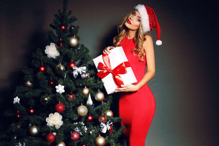 Christmas photo of sexy woman with curly blond hair in a red Santa-hat and red dress with charming smile  holding a gift-boxes near Christmas tree Stok Fotoğraf
