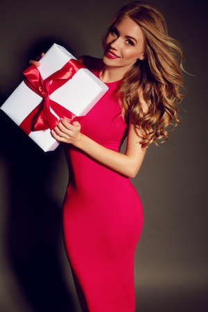 woman red dress: Christmas photo of sexy woman with curly blond hair in  pink dress with charming smile  holding a gift-box and posing in the fashion studio Stock Photo
