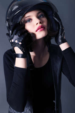 fashion studio photo of beautiful young girl with dark short hair wears biker clothes. leather jacket and helmet Stock Photo