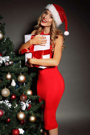 Christmas photo of sexy woman with curly blond hair in a red Santa-hat and  red dress with charming smile  holding a gift-boxes near Christmas tree