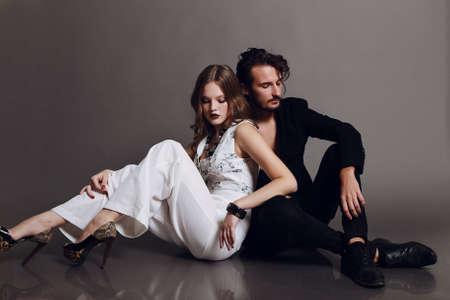 chaqueta: Estudio de moda foto de mujer morena sexy y hombre de pelo marr�n vestido con ropa de blanco y negro, abrazando y so�ando Foto de archivo
