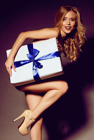 festive photo of sexy blond woman with curly hair and beautiful smile holding a Christmas present Foto de archivo