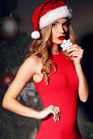 Christmas photo of sexy woman with curly blond hair in a red Santa-hat and fitting red dress holding deco near Christmas tree Foto de archivo