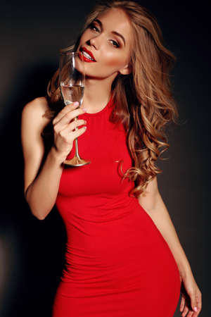 party photo of sexy lady in red dress with red lips and blond beautiful curly hair, holding a glass with shampagne