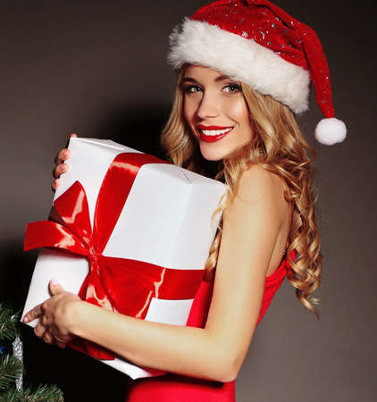 Christmas photo of sexy woman with curly blond hair in a red Santa-hat and fitting red dress with charming smile  holding a gift-boxes near Christmas tree