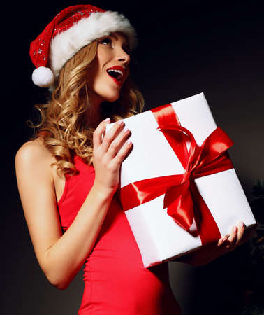 Christmas photo of sexy woman with curly blond hair in a red Santa-hat and red dress with charming smile  holding a gift-boxes near Christmas tree Foto de archivo