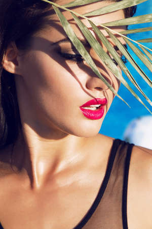 black makeup: fashion outdoor photo of sensual beautiful woman with dark hair relaxing beside swimming pool,holding a leaf on face
