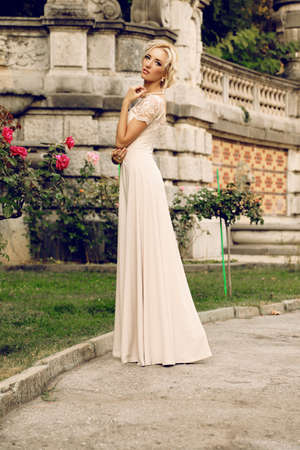 gorgeous woman: fashion outdoor photo of gorgeous bride with blond hair wears luxurious dress and accessories,posing in antic villa