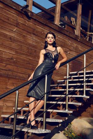 metallic stairs: fashion outdoor photo of beautiful sensual woman with dark hair wears elegant black dress,posing beside wood wall on metallic stairs Stock Photo