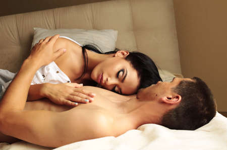passion: Fashion photo of beautiful sexy couple relaxing and embracing in the bedroom