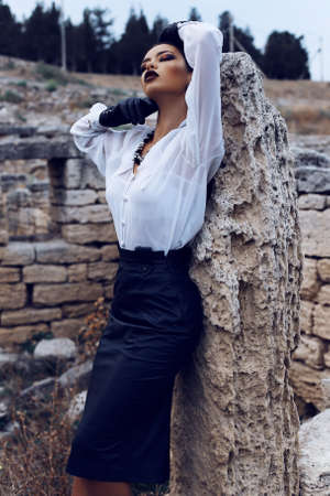 Fashion outdoor photo of sexy elegant woman with dark hair wearing a white shirt, black leather skirt and gloves posing in the old town