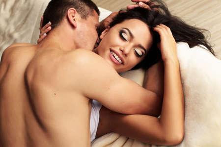 amantes en la cama: Forme la foto de una pareja apasionada atractiva relajante y besos en el hotel en una cama Foto de archivo