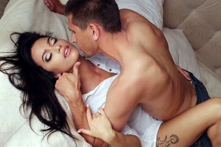 sexy couple in bed: Fashion photo of beautiful sexy couple relaxing and kissing in the bedroom