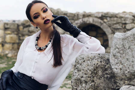 leather skirt: Fashion outdoor photo of sexy elegant woman with dark hair wearing a white shirt, black leather skirt and gloves posing in the old town