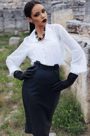 skirts: Moda foto al aire libre de la mujer elegante atractiva con el pelo oscuro con una camisa blanca, falda de cuero negro y guantes posando en el casco antiguo