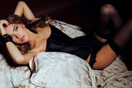moda foto interior de mujer hermosa, con el pelo largo y oscuro y rizado lleva lencería de lujo y pantimedias, posando en el dormitorio Foto de archivo