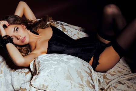 ropa interior femenina: moda foto interior de mujer hermosa, con el pelo largo y oscuro y rizado lleva lencer�a de lujo y pantimedias, posando en el dormitorio Foto de archivo