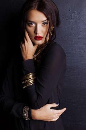 femme brune sexy: portrait en studio de mode de femme magnifique avec des cheveux noirs et le maquillage lumineux avec bijou de luxe, collier et bracelets massif