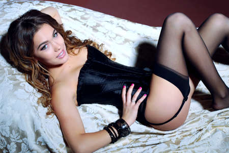 fashion interior photo of gorgeous woman with long dark curly hair wears luxurious lingerie and pantyhose,,lying in bed