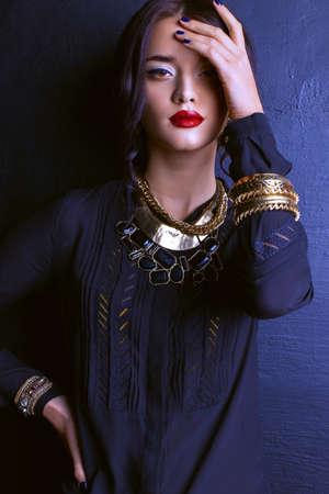 fashion studio portrait of gorgeous woman with dark hair and bright makeup with luxurious bijou, massive necklace  and bracelets Foto de archivo