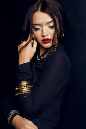 spanish girl: fashion studio portrait of gorgeous woman with dark hair and bright makeup with luxurious bijou, massive necklace  and bracelets Stock Photo