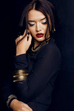 Fashion studio portret van prachtige vrouw met donker haar en lichte make-up met luxe bijou, massieve ketting en armbanden