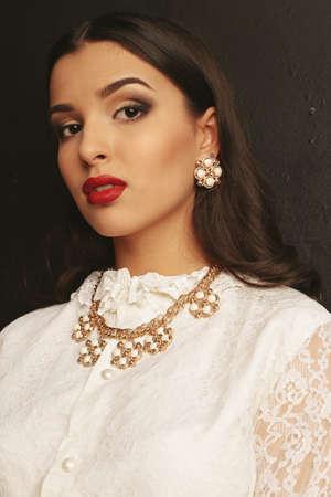 bijou: fashion studio portrait of gorgeous woman with dark hair and bright makeup with luxurious bijou, wears elegant lace blouse