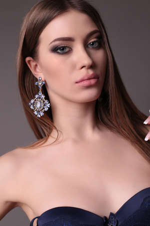 bijou: fashion studio portrait of gorgeous woman with dark hair and bright makeup with luxurious bijou Stock Photo