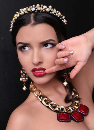 bijou: fashion studio portrait of gorgeous woman with dark hair and bright makeup with luxurious bijou, massive necklace and headband