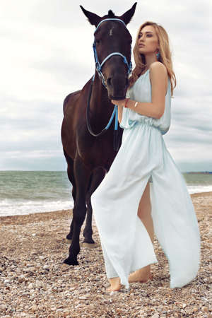 accessories horse: fashion outdoor photo of beautiful young woman with long blond hair wears elegant dress, posing with black horse,walking by autumn beach Stock Photo