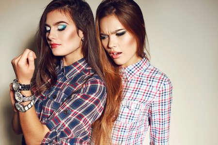 mujeres elegantes: Foto de la manera de dos hermosas mujeres jóvenes con el pelo largo y oscuro y maquillaje brillante viste ropa casual, posando en el estudio Foto de archivo