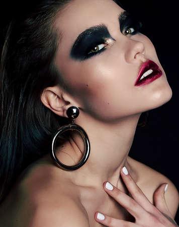 black makeup: fashion studio portrait of beautiful woman with dark hair and extravagant black smokey eyes makeup Stock Photo