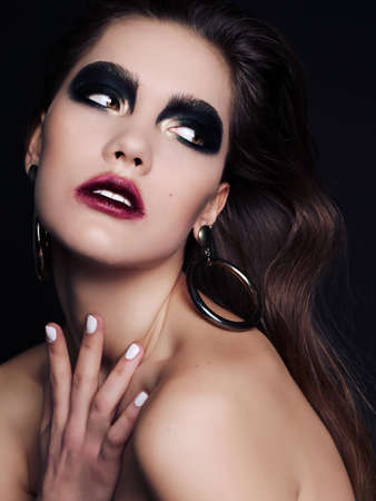 extravagant: fashion studio portrait of beautiful woman with dark hair and extravagant black smokey eyes makeup Stock Photo