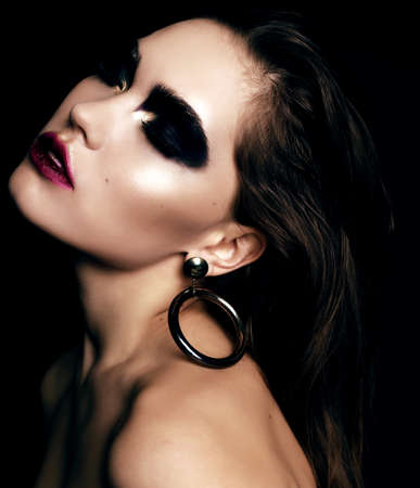 fashion studio portrait of beautiful woman with dark hair and extravagant black smokey eyes makeup Stock Photo